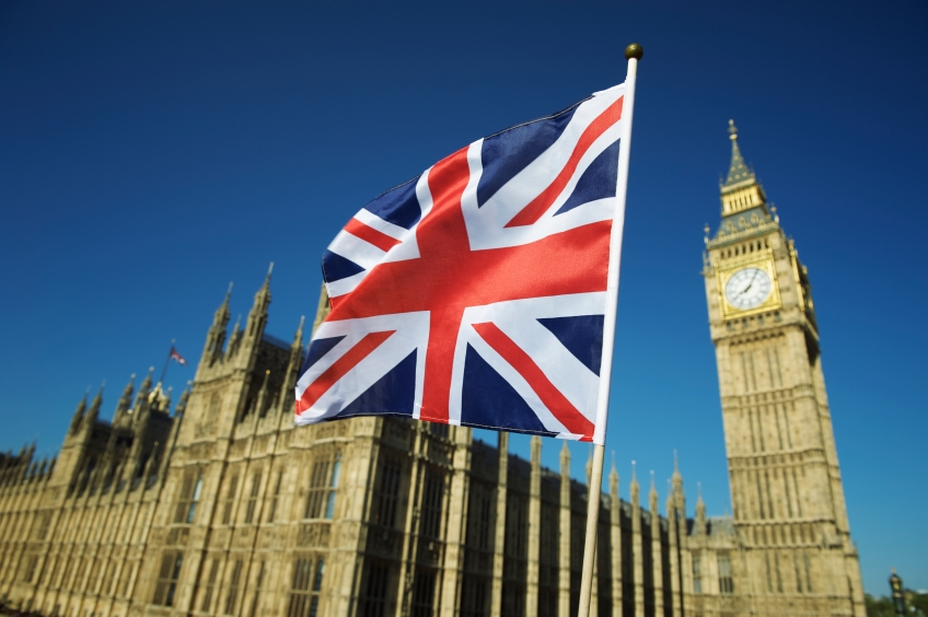 Union Jack British flag flies in bright blue sky at Houses of Parliament and Big Ben London